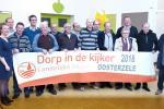 Een fier bestuur van LG Oosterzele pronkt met de aankondigingsbanner Dorp in de Kijker 2018.