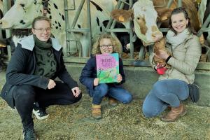Op de foto: boerin Ann van hoeve de Peinwinning, schrijfster Ilse en haar zoontje Alberic (Basiel in het boek), hondje Muyshondt (Tokkel in het boek) in de stal bij hoeve de Peinwinning